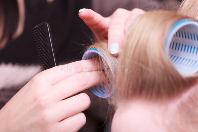Salón de belleza femenino del peluquero de los rodillos de los bigudíes de la cabeza del pelo rubio fotografía de archivo