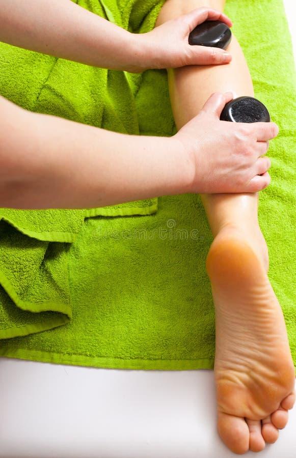 Salón de belleza. Mujer que consigue a balneario masaje de piedra caliente de las piernas foto de archivo