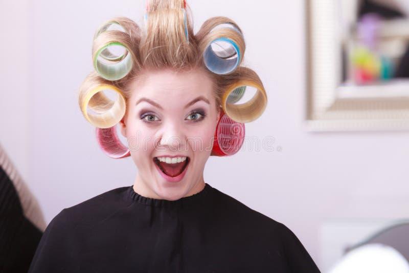Salón de belleza rubio feliz alegre del peluquero de los rodillos de los bigudíes de pelo de la muchacha fotografía de archivo