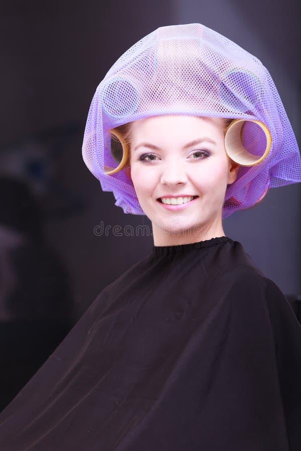 Salón de belleza rubio hermoso del peluquero de los rodillos de los bigudíes de pelo de la muchacha del retrato imágenes de archivo libres de regalías