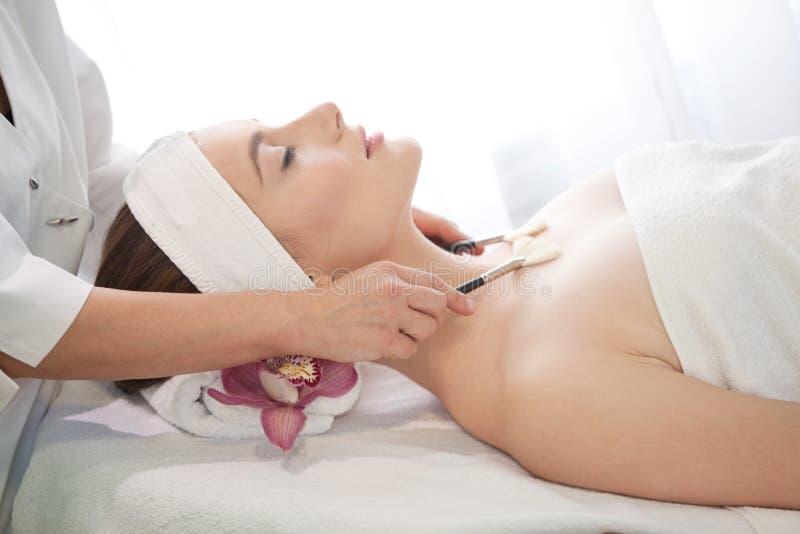 Salón del balneario: Mujer hermosa joven que tiene masaje facial foto de archivo libre de regalías