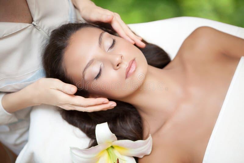 Salón del balneario: Mujer hermosa joven que tiene masaje facial foto de archivo