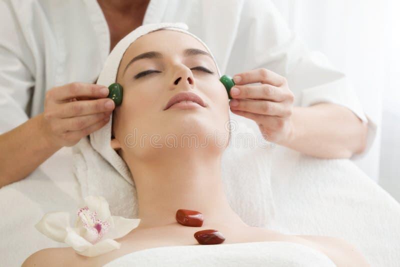 Salón del balneario: Mujer hermosa joven que tiene masaje facial con Ston fotos de archivo libres de regalías