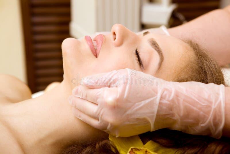 Salón del balneario: Mujer joven hermosa que tiene masaje de cara imagen de archivo