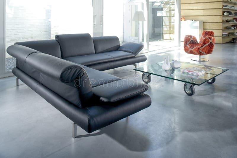 Salón elegante con el sofá de la esquina cómodo gris en un hou moderno foto de archivo libre de regalías