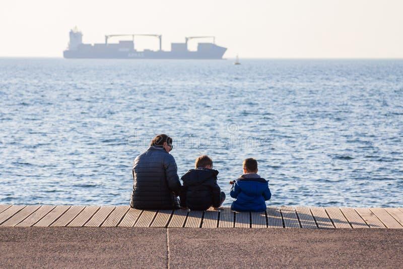 SALÓNICA, GRECIA - 25 DE DICIEMBRE DE 2015: La abuela y sus nietos que descansan sobre la orilla del mar, un buque de carga puede imagen de archivo libre de regalías