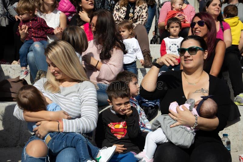 Salónica, Grecia - 4 de noviembre de 2018: Madre que amamanta a su bebé en el 9no por toda la nación amamantamiento público en la foto de archivo