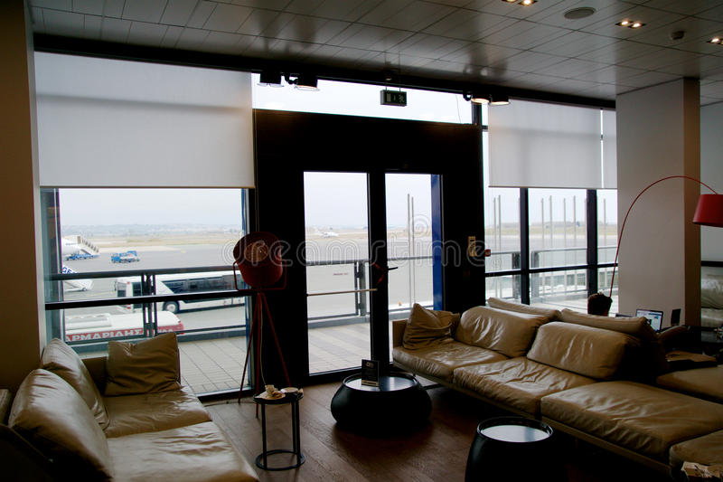 SALÓNICA, GRECIA - 16 de octubre de 2016: interior del aeropuerto, salón del viajero frecuente con el sofá de cuero y vista del d imagen de archivo libre de regalías