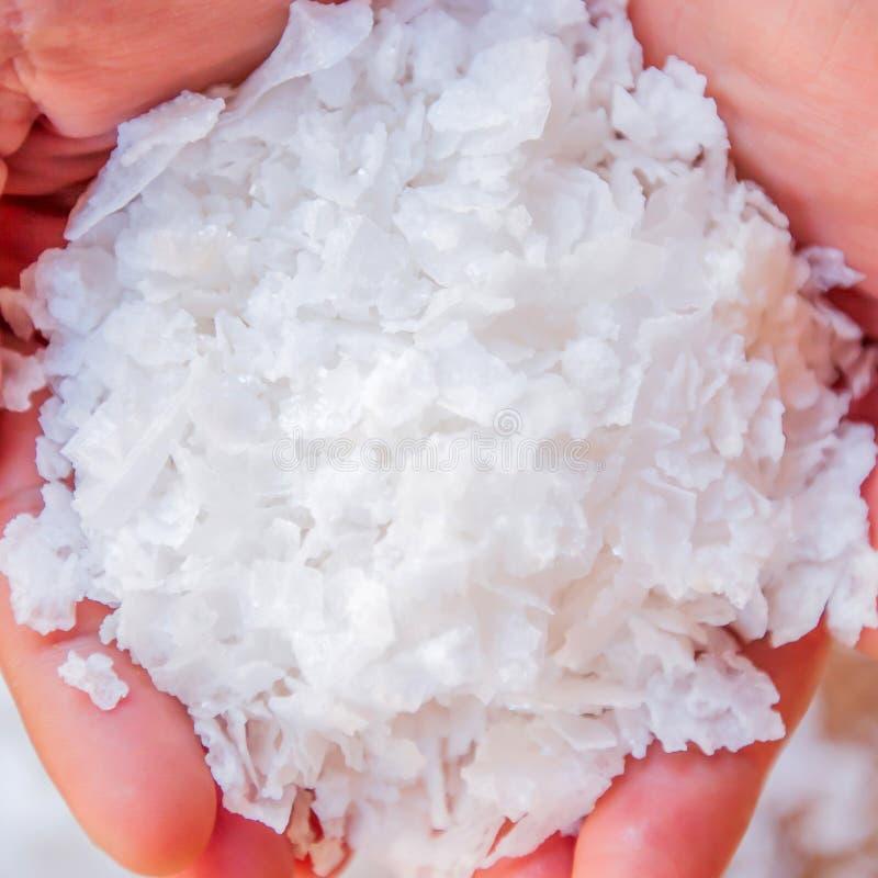 Sal blanca pura de los cristales, sal de roca en manos de las mujeres en fondos de los cristales Visi?n superior, primer Sal de r fotos de archivo