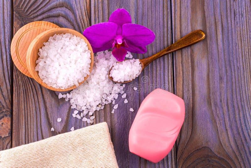 Sal de banho branco em um copo de madeira com uma colher em uma tabela de madeira w foto de stock