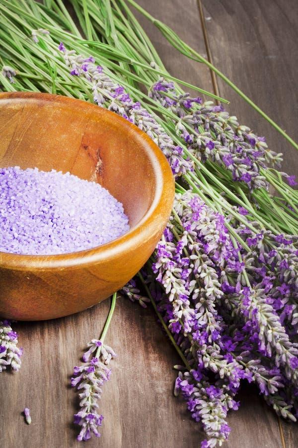 Sal de banho violeta com alfazema fresca no fundo de madeira imagem de stock
