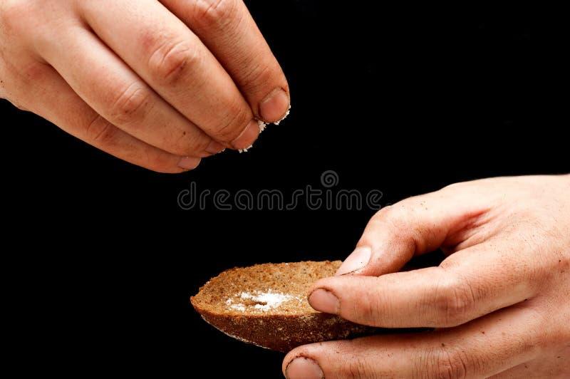 Sal de derramamento do pobre homem com mãos sujas foto de stock