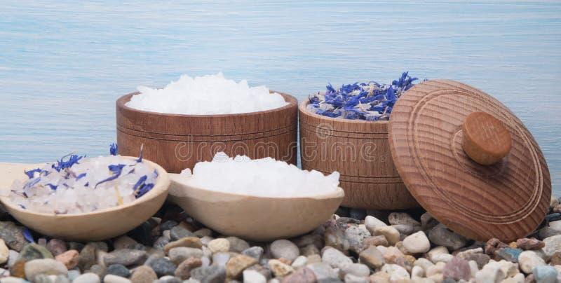 Sal del mar con la adición de las flores azules, en pequeñas piedras, en un fondo azul fotos de archivo libres de regalías