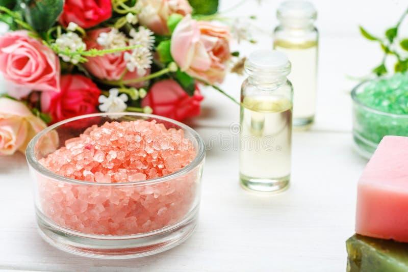 Sal do Mar Vermelho, duas garrafas com óleo cosmético e flores cor-de-rosa em uma tabela de madeira branca fotografia de stock royalty free