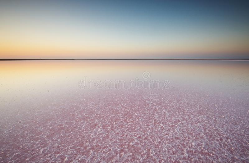 Sal e salmoura de um lago cor-de-rosa, coloridos pelo salina de Dunaliella dos microalgae no por do sol imagem de stock royalty free
