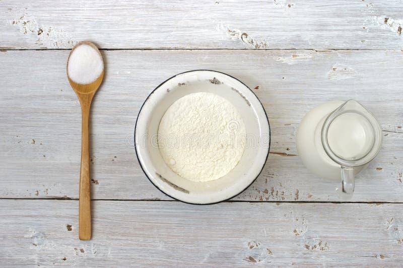 Sal, harina y un jarro de leche en la tabla blanca imágenes de archivo libres de regalías