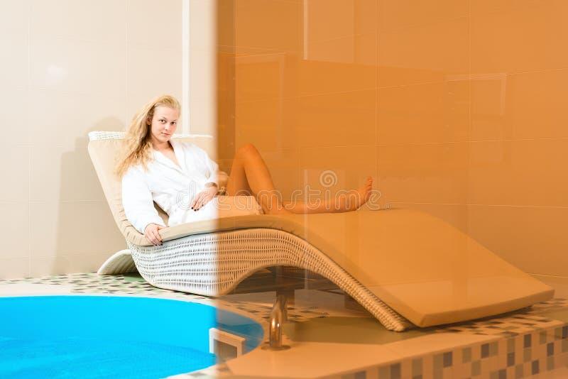 Sal?o de beleza dos termas a moça de encantamento relaxa em um sofá pela associação mulher no revestimento branco que encontra-se foto de stock