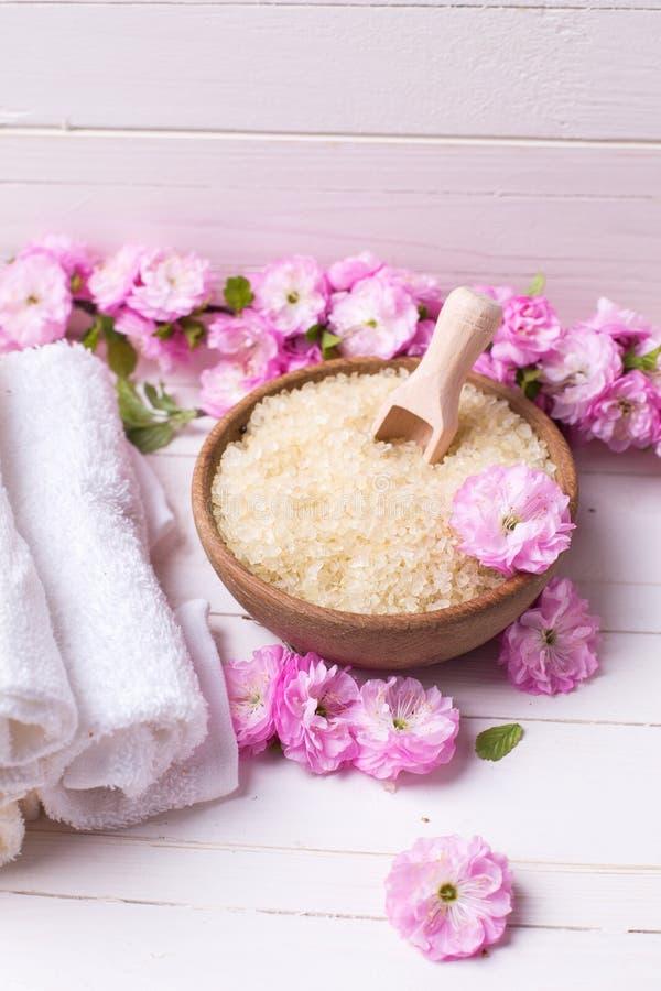 Sal orgánica del mar en cuenco con las toallas y las flores rosadas imagenes de archivo