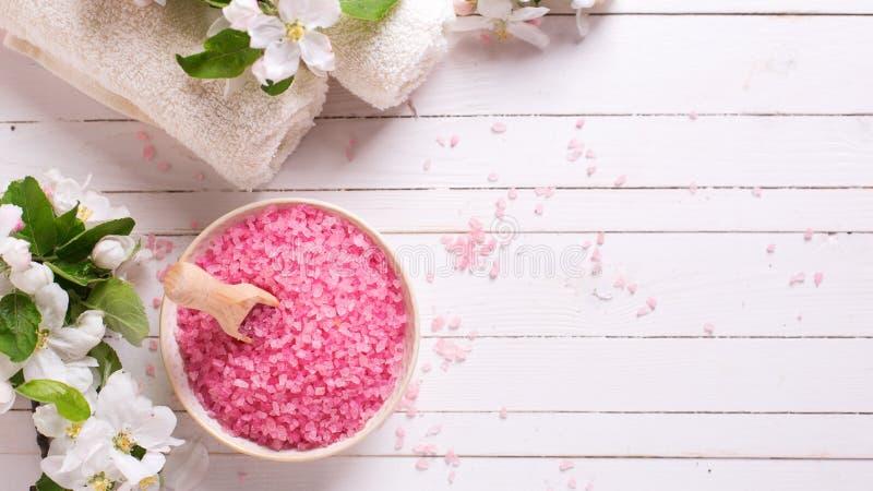 Sal rosada del mar en cuenco, toallas y flores en el backg de madera blanco fotos de archivo libres de regalías