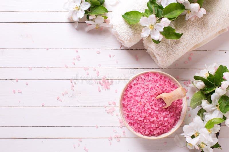 Sal rosada del mar en cuenco, toallas y flores en el backg de madera blanco foto de archivo