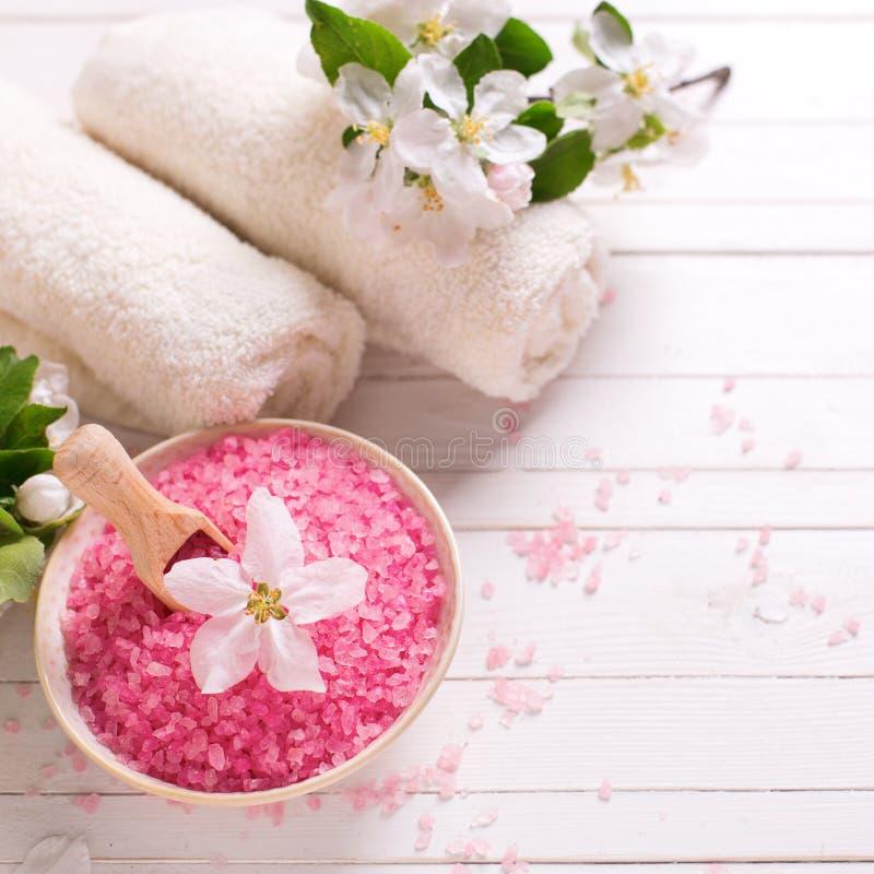 Sal rosada del mar en cuenco, toallas y flores en el backg de madera blanco imágenes de archivo libres de regalías