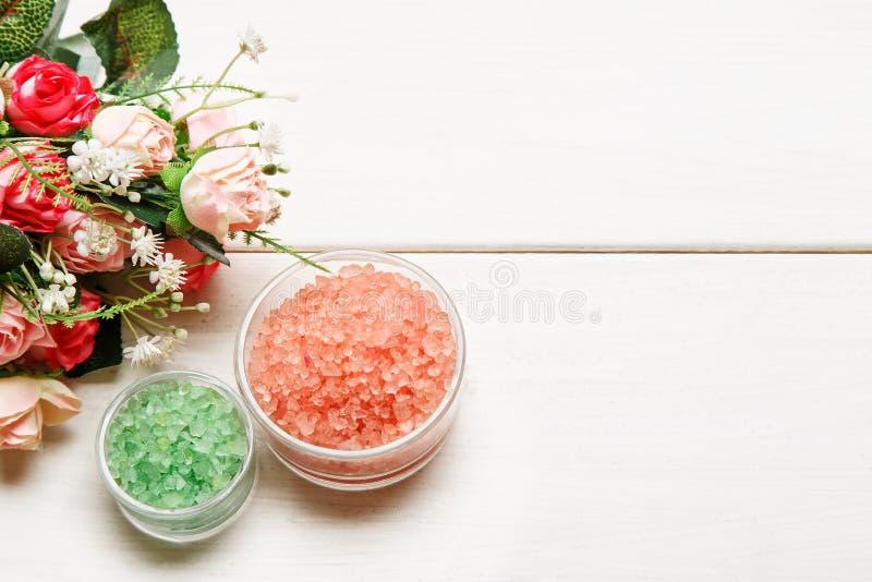 Sal verde y rosada del mar en bol de vidrio con las flores color de rosa en una tabla de madera blanca, visión superior, espacio  fotos de archivo libres de regalías