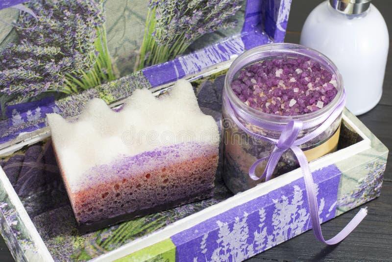 Sal y esponja de baño púrpuras en una caja imagenes de archivo