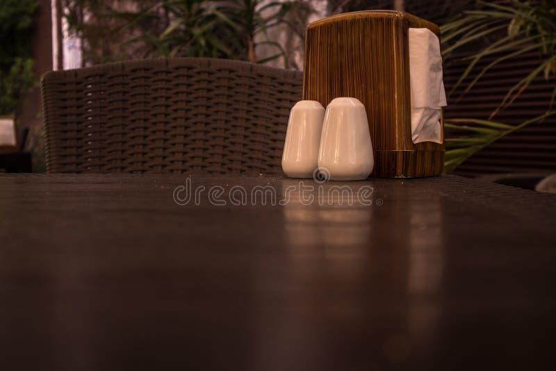 Sal y pimienta en la tabla del restaurante imagen de archivo