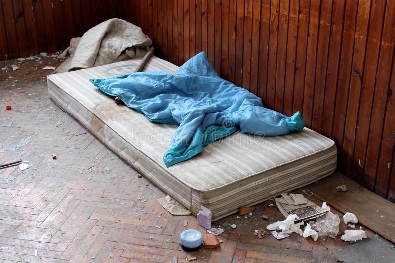 Sala abandonada com colchão e lixo fotografia de stock royalty free