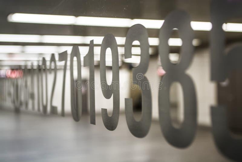 sala Branco-cinzenta Iluminação em um corredor longo Paredes leves, espelho com números, e assoalho luster Fundo fotografia de stock