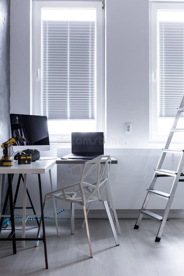 Sala brilhante com computador e robôs imagem de stock