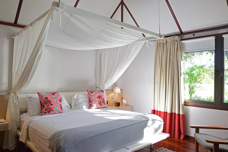 Sala brilhantemente iluminada da cama de uma casa de madeira moderna no país tropical fotografia de stock