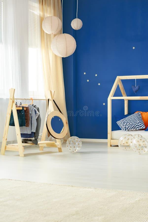 Sala com a cremalheira da roupa das crianças imagem de stock