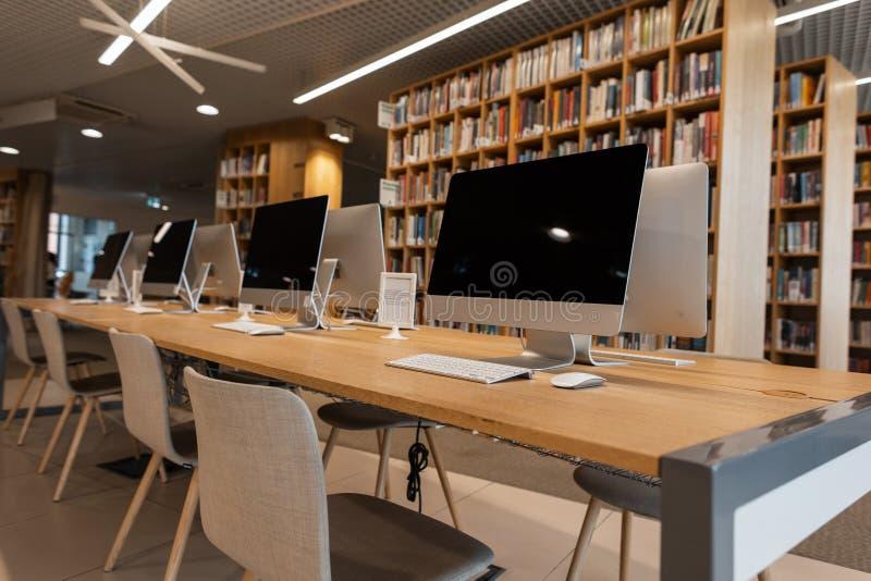 Sala com os computadores brancos modernos em uma biblioteca da universidade ou de faculdade Classe do computador imagens de stock royalty free