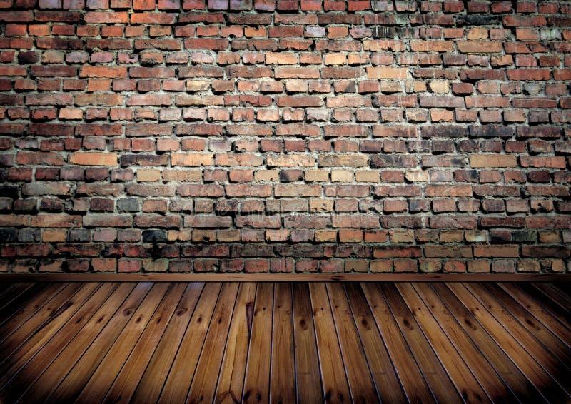 Sala com parede de tijolo e o assoalho de madeira fotos de stock royalty free