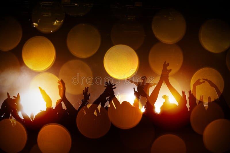 Sala da concerto con una fase accesa e siluette della gente durante il concerto immagine stock libera da diritti