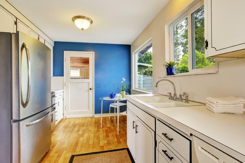 Sala da cozinha com os armários brancos, as paredes azuis e o vidro capazes fotografia de stock royalty free
