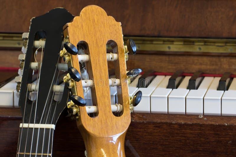 Sala da prática de música Headstock da guitarra acústica e close-up do piano fotos de stock royalty free