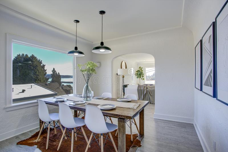 Sala da pranzo con le pareti bianche e la tavola di legno fotografia stock