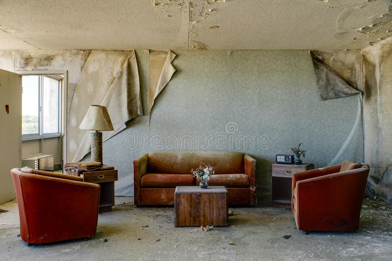 Sala de alojamento intacto com as cadeiras & o sofá alaranjados queimados - hotel abandonado fotografia de stock royalty free