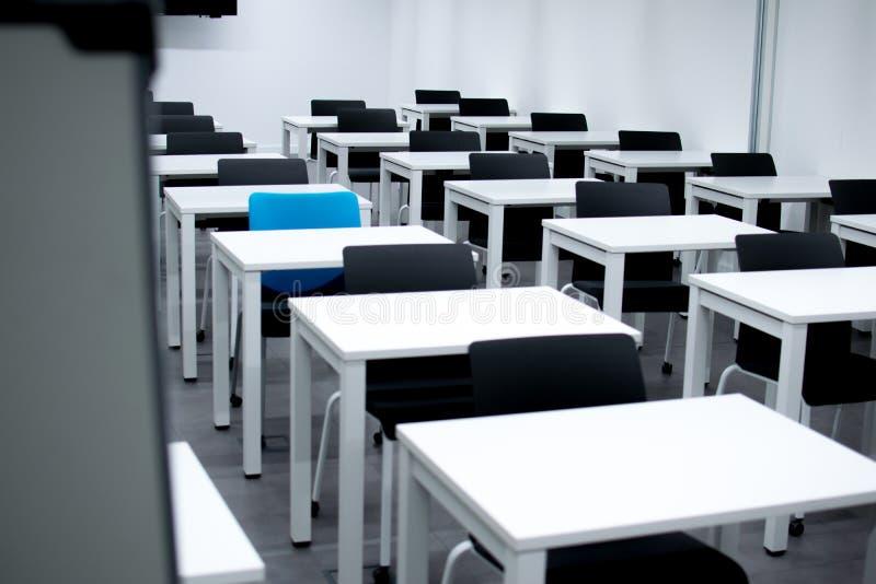 Sala de aula com cadeiras pretas e a uma cadeira azul Contratando, vago ou escolhendo o conceito foto de stock