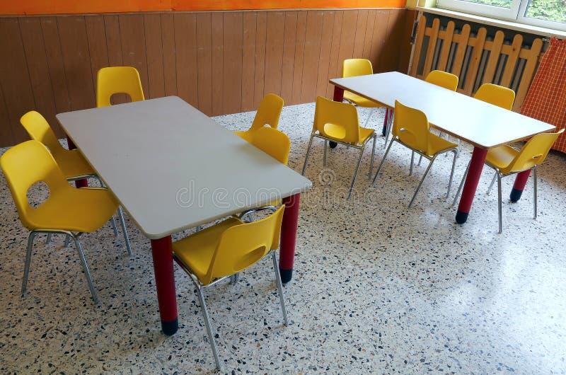 Sala de aula do jardim de infância com mesas e as cadeiras amarelas fotografia de stock royalty free