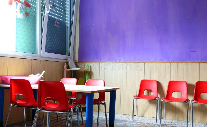 Sala de aula do jardim de infância com mesas e as cadeiras vermelhas sem crianças imagens de stock