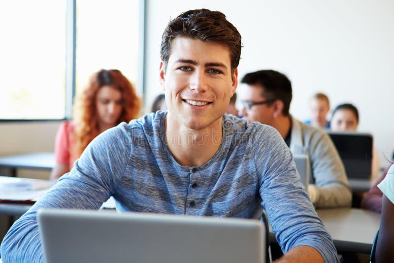 Sala de aula masculina de Using Laptop In da estudante universitário imagens de stock royalty free