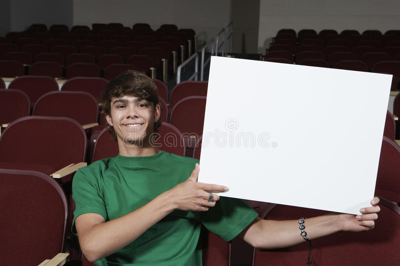 Sala de aula nova de Holding Billboard In do estudante masculino fotografia de stock