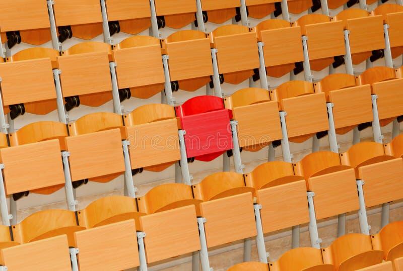 Sala de aula vazia com cadeiras de madeira e a uma cadeira vermelha imagens de stock