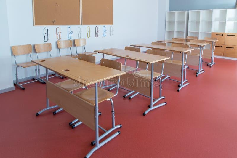 Sala de aula vazia com mesas e as cadeiras de madeira imagem de stock