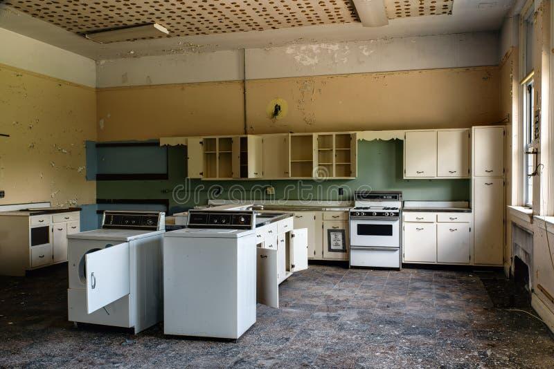 Sala de clase abandonada de la economía doméstica de la escuela con la lavadora, el secador y las estufas fotos de archivo libres de regalías