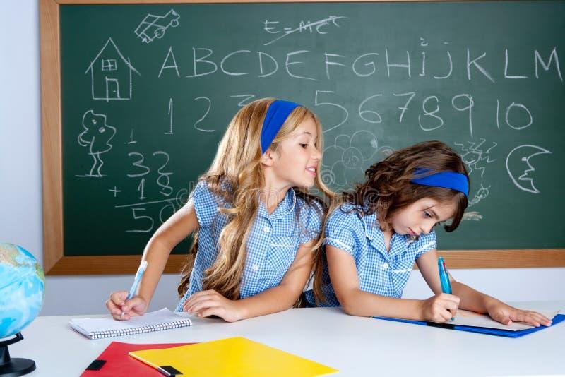 Sala de clase con dos estudiantes de los cabritos que engañan en prueba fotografía de archivo libre de regalías