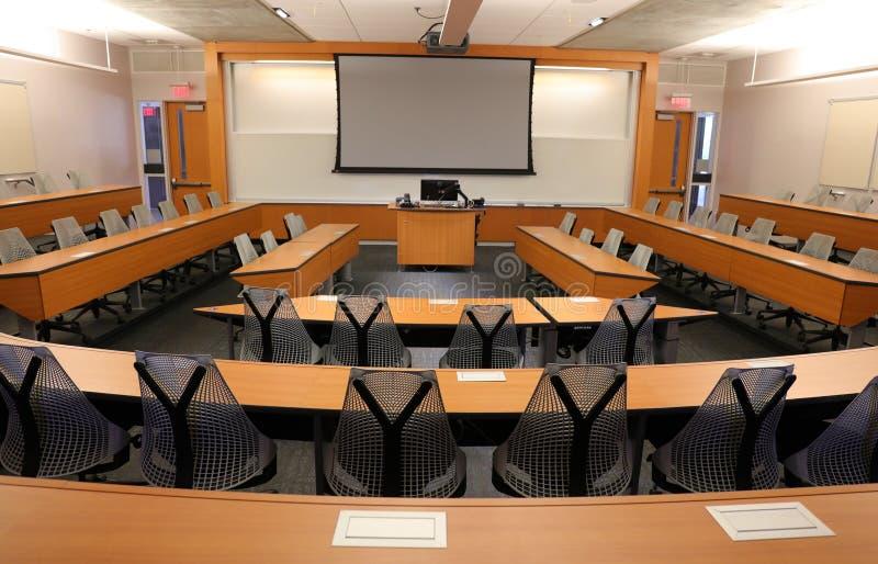 Sala de clase vacía con el proyector y la pantalla en blanco fotografía de archivo libre de regalías
